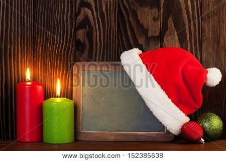 Christmas chalkboard, candles and santa hat in front of wooden wall with copy space