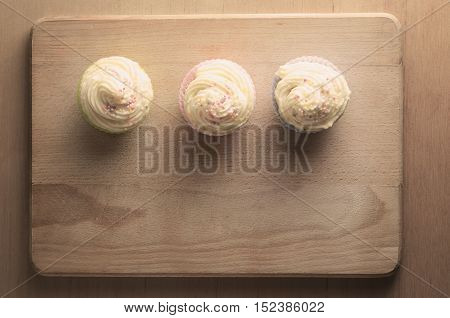 Overhead shot of three cupcakes in a row on a wooden chopping board topped with swirls of buttercream icing and colourful sprinkles. Retro hues.