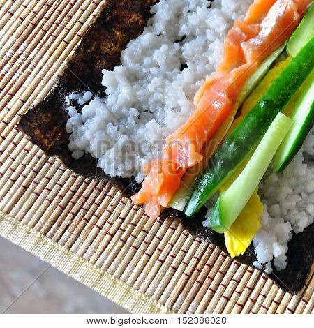 The process of making homemade sushi. Nori rice red fish cucumber eggs are laid on the wooden napkin. View from above.