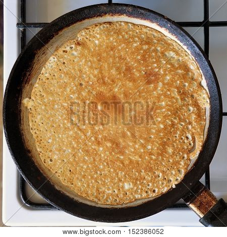 The process of making pancakes. Kitchen stove with a frying pan with thin pancakes. View from above.