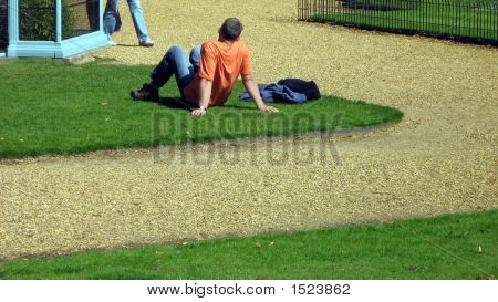 A Man Sitting Alone On The Grass Enjoying The Sun.Holiday