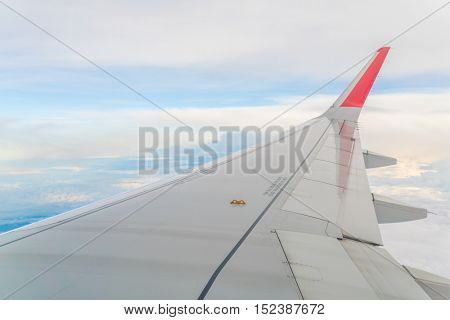 Wing of an airplane flying above the clouds
