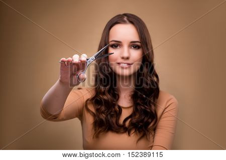 Beautiful woman with scissors cutting her hair