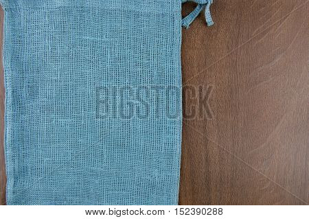 Sack from left side wooden table. Soft blue woven linen fabric texture / wood texture. Coarse jute sack.  Top view background.