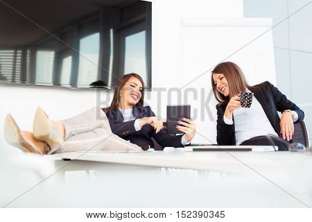 Cute young female workers are resting in office