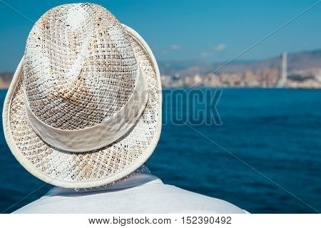 Rear view of unrecognizable person in straw hat standing against seascape