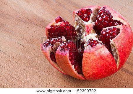 ripe pomegranate on wood background. fresh fruit