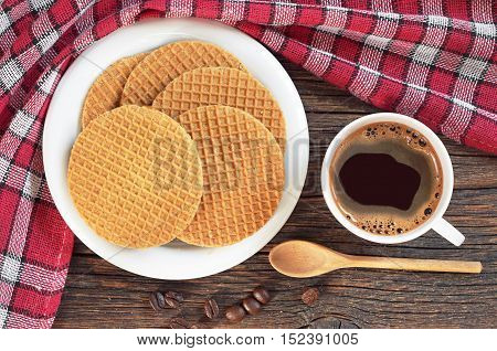 Cup of hot coffee and round waffles on dark wooden table with red tablecloth top view