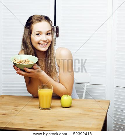 portrait of happy cute girl with breakfast, green apple and orange juice smiling