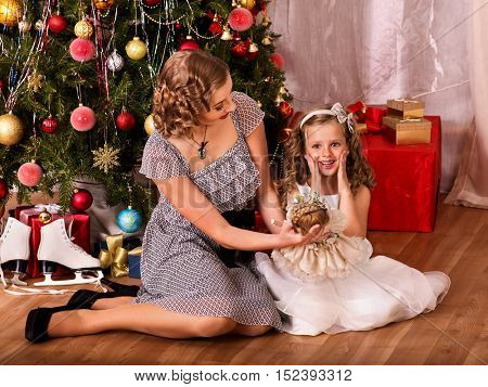 Child with mother receiving near Christmas tree. Mom gives daughter Christmas doll.