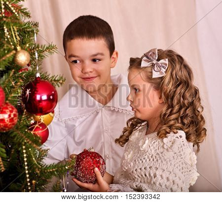 Children receiving gifts under Christmas tree. Brother and sister together.