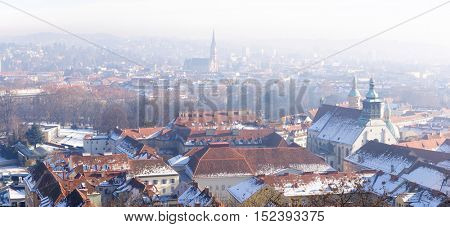 A panoramic view of the old town from the Grazer Schlossberg  in  frosty winter morning, Graz, Austria. In the background Church of the Sacred Heart of Jesus