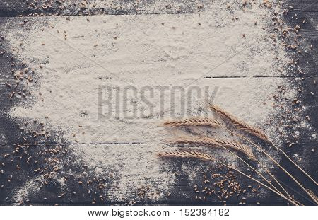 Baking class or recipe concept on dark background, sprinkled wheat flour, grain and ears with free copy space. Top view on wooden board or table. Cooking dough or pastry.