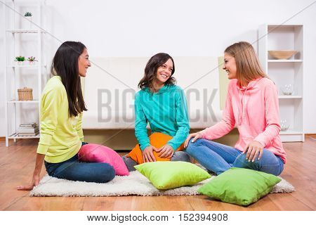 Three friends are sitting in room and talking.