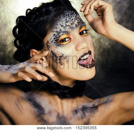 fashion portrait of pretty young woman with creative make up like a snake, halloween look close up