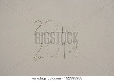 Message 2016 and 2017 written on sand at the beach. 2016 almost washed away by wave symbolizing changing of years. New year postcard