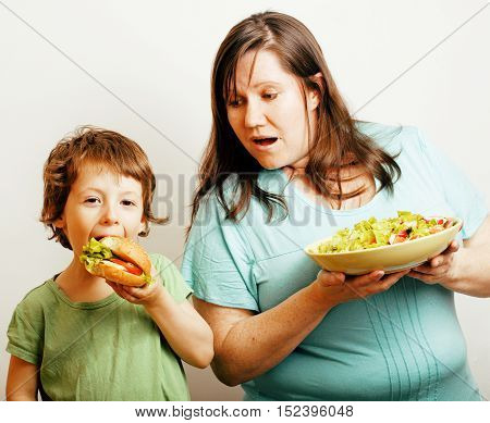 mature woman holding salad and little cute boy with hamburger teasing close up, family food, lifestyle real people concept isolated