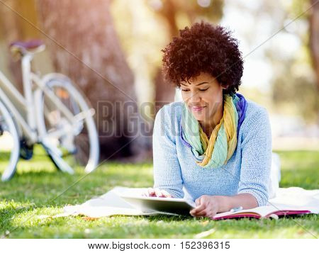 Young woman using tablet in the park.