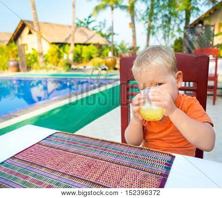 Child drinking juice near a swimming pool