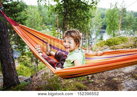 little cute real boy in hammock smiling against landscape with forest and lake hight on mountain, lifestyle people concept close up
