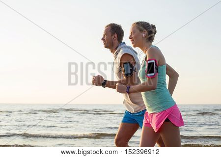 Couple running on the beach and listening music