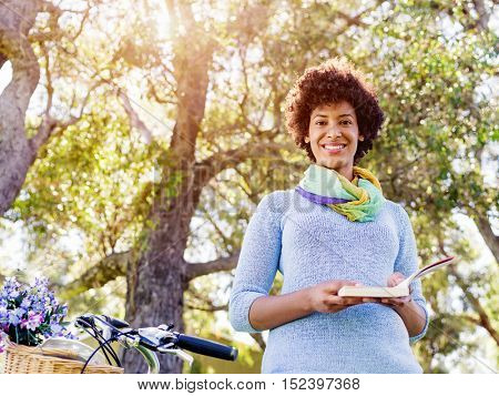 Happy young woman with bicycle reading book