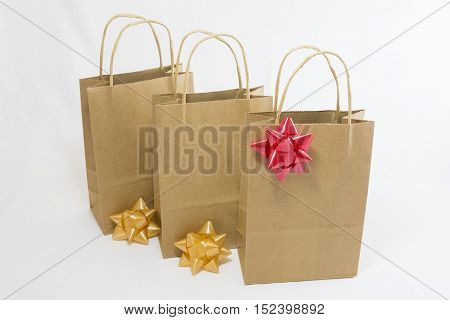 Three plain paper shopping bags with simple bows