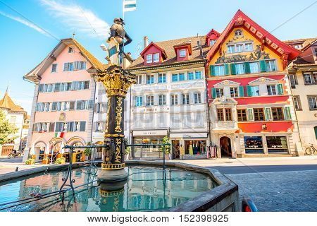 Zug, Switzerland - June 28, 2016: Fountain with colorful buildings on the central square in Zug town near Zurich city in Switzerland