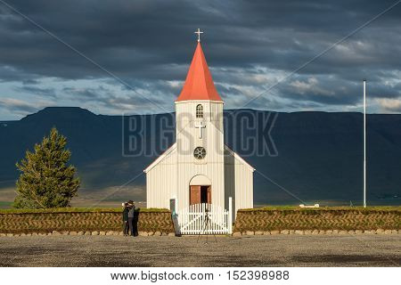 GLAUMBAER, ICELAND - AUGUST 16, 2016: Tourists take photos at Glaumabaer church. This is a popular tourist stop between Saudarkrokur and Varmahlid in Iceland.