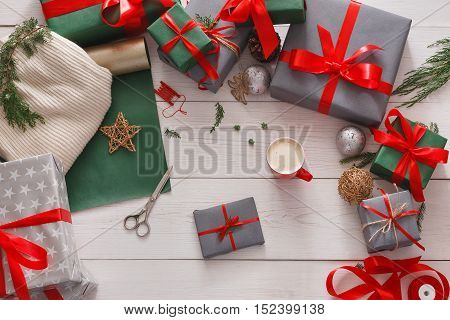 Gift wrapping background. Boxes on white wood background. Stylish modern presents in gray and green paper decorated with red satin ribbon bows. Christmas and winter holidays concept, top view