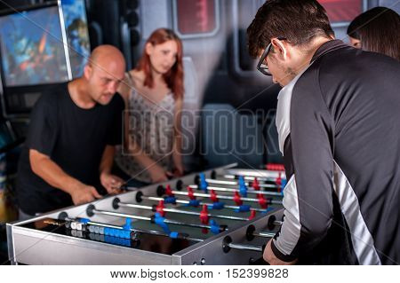 Group of friends playing soccer table foosball