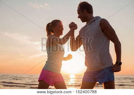 Fit and happy couple on the beach showing their strength