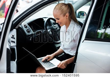 Businesswoman sitting on drivers seat in car and working with laptop