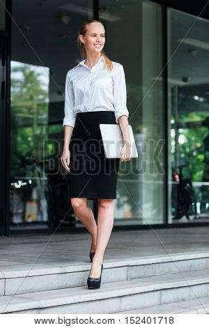 Full length of a smiling blonde businesswoman with laptop get down stairs