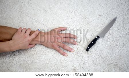 hand of man tryning to grab a knife while woman holding his arm