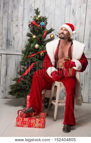 Handsome and charming bad Santa Clause is bad boy, who is dream of any housewife. Happy Santa Clause drinking alcohol drinks and smoking.