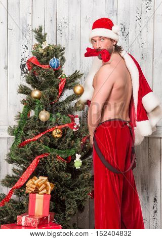 Bad Santa Clause looking surprised while posing naked for photographer isolated on white background in studio.