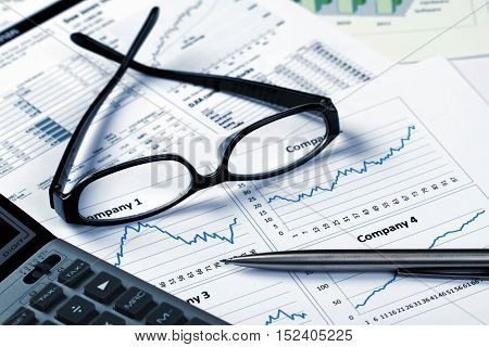 Glasses, Pen And Calculator On Financial Graphs Close-up