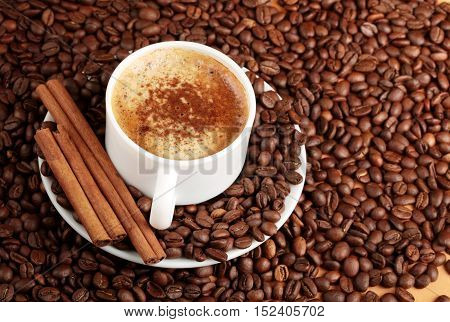 Cappuccino or latte surrounded by coffee beans and cinnamon sticks