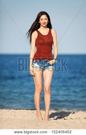Young beautiful fashion woman standing on the beach. Happy outdoor summer lifestyle. Vacation. Ocean beach relax. Sexy stylish woman with long hair in jean shorts and red top walking at the beach