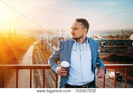 Man with Cup of coffee on the bridge. Early morning, the sunrise, the road disappears in the distance