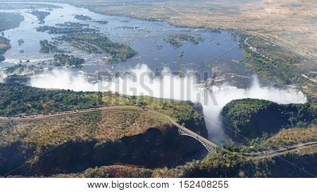 View from the air to the Victoria Falls, border bridge between Zambia and Zimbabwe over a canyon, Zambezi River with wooded islands