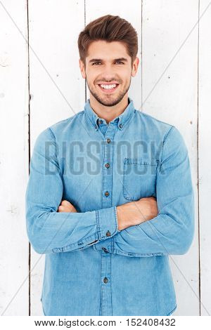 Portrait of a happy casual man standing with arms folded over white background and looking at camera