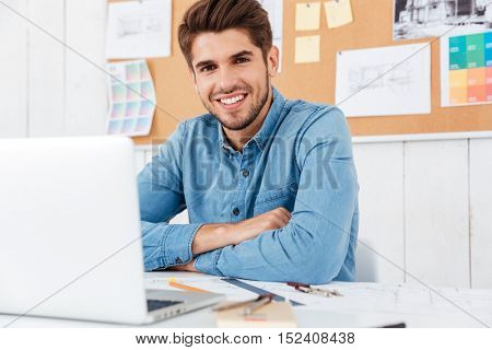 Happy smiling businessman sitting at the table with arms folded at the office
