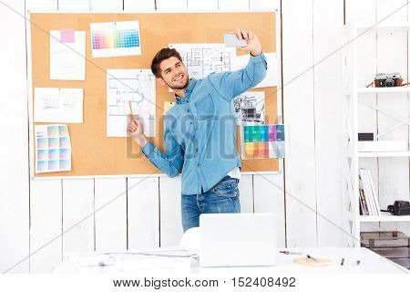Smiling young businessman making selfie while standing in front of task board at office