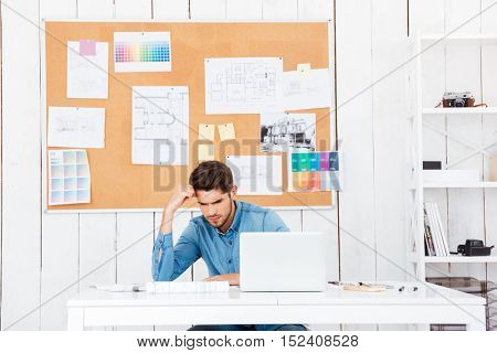 Young tired businessman sitting with laptop at the desk in office