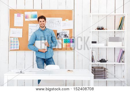 Cheerful young man standing at the task board and holding laptop in office