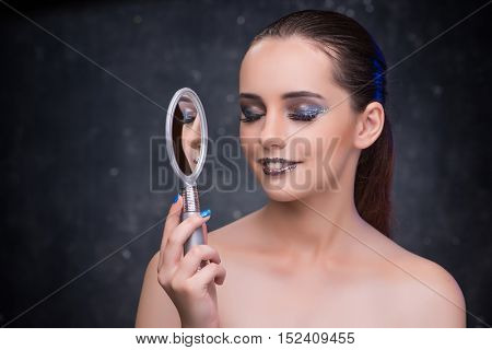 Young woman with small mirror in beauty concept
