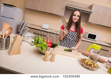 Young woman housewife working in the kitchen