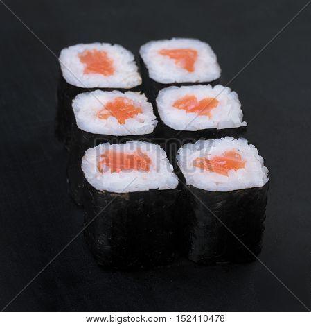 Salmon nori rolls on a black background